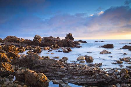 water stone: A wide shot of Corona Beach in Newport Beach California during sunset