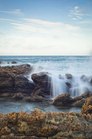 A shot of an early morning Corona Beach in Newport Beach California with the surf crashing into rocks. Stock Photo