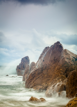 A shot of waves crashing on the rocky shore of Corona Beach on a cold and windy day Banque d'images
