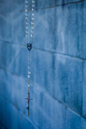 A close up of a rosary hanging in front of a gray cinder block wall