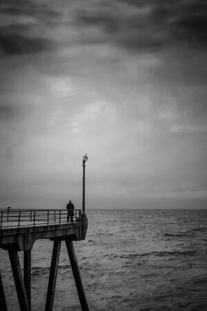 Un tir en noir et blanc d'un homme debout à la fin d'une jetée regarder une tempête. Banque d'images