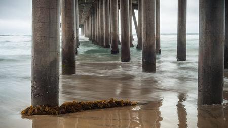 Un tir à la recherche de sous la Huntington Beach Pier lors d'une tempête d'hiver avec des algues dans le premier plan. Banque d'images