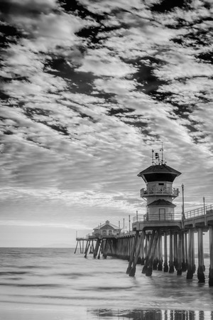 A black and white shot of the Huntington Beach Pier right before sunset.