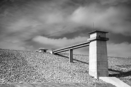 A black and white shot of a utilty building at the top of a dam.