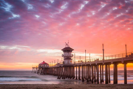 A wide shot of the Huntington Beach Pier during a bright and colorfull sunset.