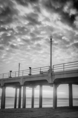 A black and white shot of the Huntington Beach Pier during sunset.