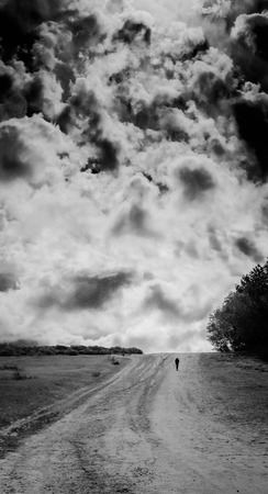 A black and white shot of a lone person walking on a dirt road. Banque d'images
