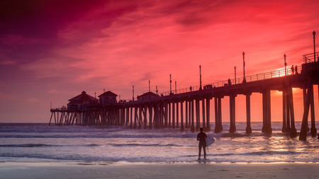 A wide shot of a surfer  looking for a good set of waves and the Huntington Beach Pier in the background  Stock Photo