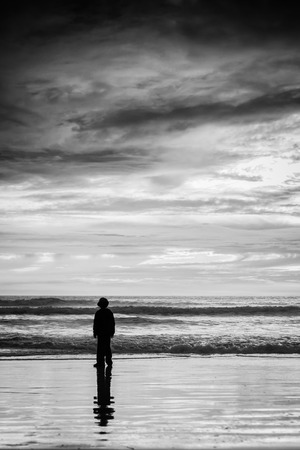 A black and white shot of a young boy looking at the waves coming into the beach