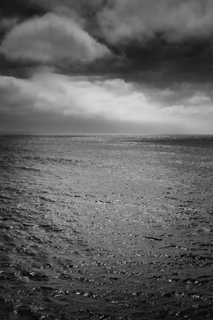 A black and white shot of the Pacific Ocean with a storm in the background