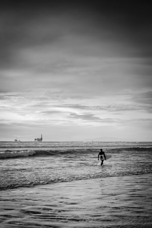 A black and white shot of a surfer walking on the beach looking for a good set of waves