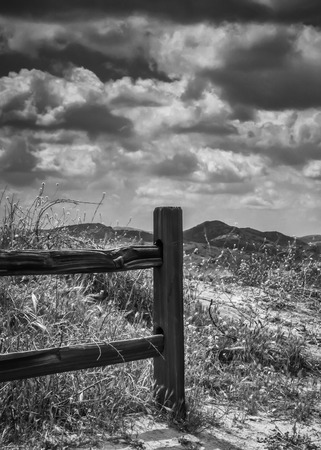 A black and white shot of the countryside with a wood fence in the foreground