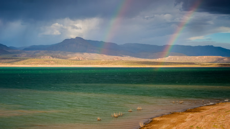 A wide shot of Lake Roosevelt  on a stormy day with a double rainbow in the background