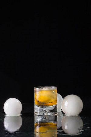 A studio shot of a lowball glass of whiskey with an ice ball in the glass and surrounded by ice  balls with a black background