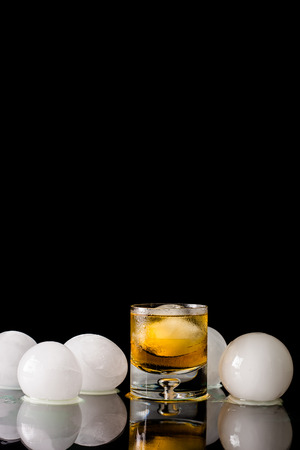 BARWARE: A studio shot of a lowball glass of whiskey with an ice ball in the glass and surrounded by ice  balls with a black background