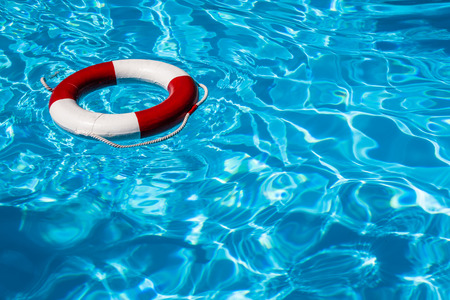A close up shot of a life guards red and white rescue ring buoy floating in a pool  Banque d'images