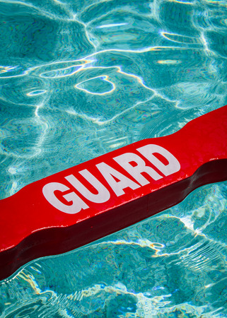 A close up shot of a life guards red and white rescue tube floating in a pool  Banque d'images