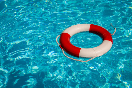 A close up shot of a life guards red and white rescue ring buoy floating in a pool  Stock Photo