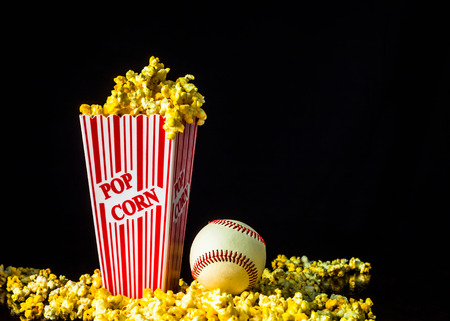 A close up shot of a classic box of red and white striped popcorn box with a baseball isolated against a black background.