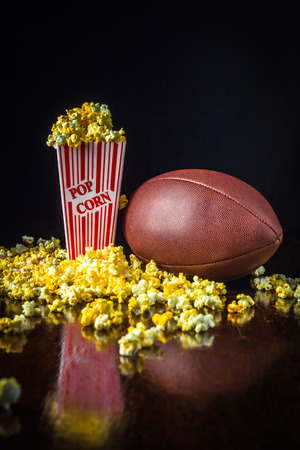 A close up shot of a classic box of red and white striped popcorn box with a fooball isolated against a black background. Banque d'images