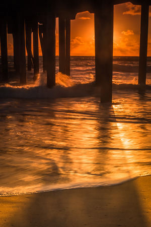 A sunset shot looking out to the Pacific Ocean under the Huntington Beach Pier.