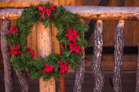 hand rail: A close up of a Christmas wreath hung on an old west wood hand rail. Stock Photo