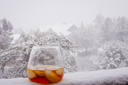 A close up of an glass of whiskey  sitting on a snow covered railing. Banque d'images