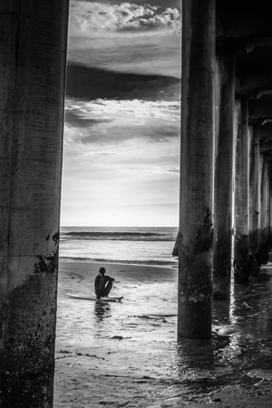 A shot looking though the Huntington Beach Peir at a surfer looking dejected.
