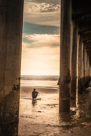 Un tir regardant si le Huntington Beach Peir à un internaute à la recherche déprimé.