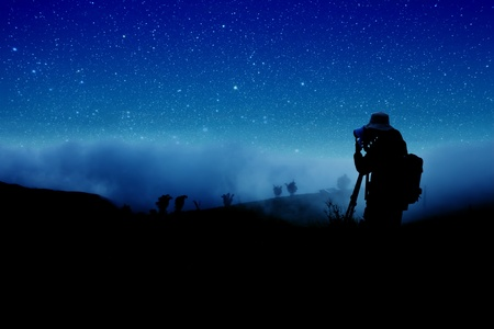 silhouette of photographer shooting night stars  photo