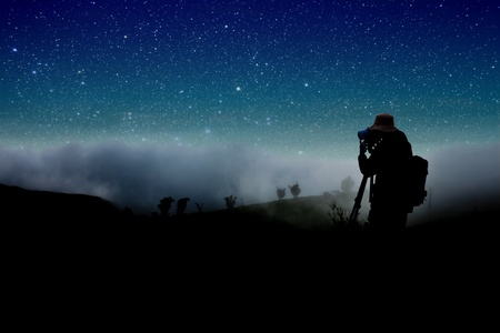 night landscape: silhouette of photographer shooting night stars