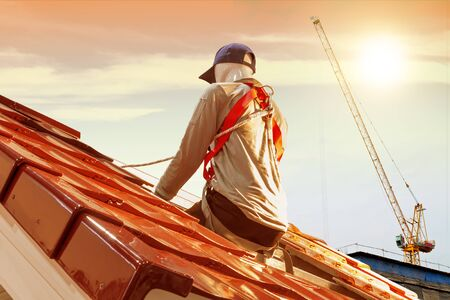 Roof repair, men model worker replacing tiles on the roof house with sunlight background