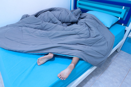 Child sleep in bed with Legs sticking out from under the blanket in the bedroom 스톡 콘텐츠