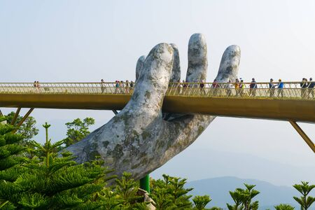 "Danang, Vietnam - Mar. 29, 2019: The Golden Bridge ""giant hands of Gods"". The two giant colossal hands emerging from the mountains holding up the golden bridge at the height of 1,414 m from the sea level in the Ba Na Hills, Da Nang, Vietnam. Editorial"