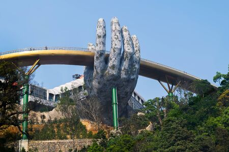 "Danang, Vietnam - Mar. 29, 2019: The Golden Bridge ""giant hands of Gods"". The two giant colossal hands emerging from the mountains holding up the golden bridge at the height of 1,414 m fro 報道画像"