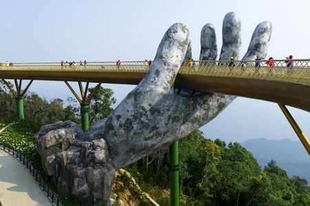 Da Nang, Vietnam - Mar. 29, 2019: The Golden Bridge. The two giant colossal hands emerging from the mountains holding up the golden bridge at the height of 1,414 m from the sea level in Ba Na Hills. 報道画像