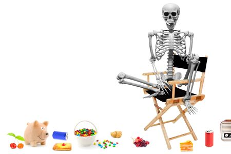 Fake human skeleton sitting on director chair with various items on the floor.halloween concept. 写真素材