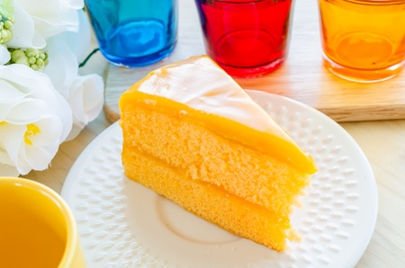 Orange cake in white dish on the wood table photo