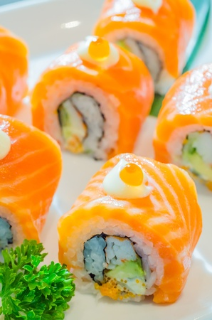 Salmon roll sushi with salmon egg on top in white dish photo