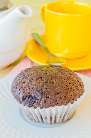 Chocolate banana cupcake on white dish with teapot&yellow tea cup photo