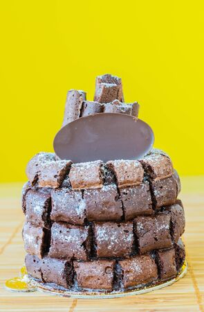 Chocolate cake with choco stick roll on the bamboo table&yellow background photo