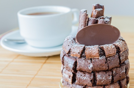 Chocolate cake with choco stick roll on the bamboo table with white tea cup&tea pot photo
