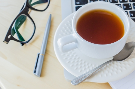 white cup tea&laptop on the wood table photo