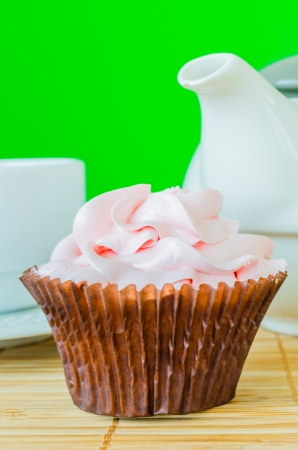 Pink cupcake on the table with colorful background photo