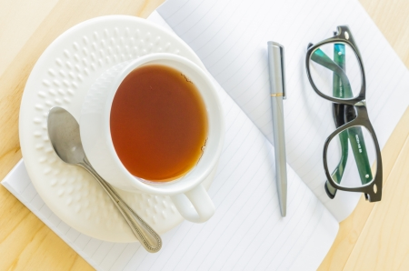 Paper note with eye glasses&white cuptea photo