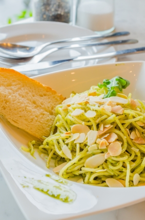 Spaghetti with bread in white dish on the stone table photo