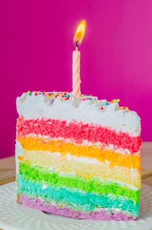 Rainbow cake with candle on white dish