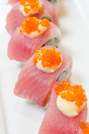Tuna sushi with avocado inside on white dish photo