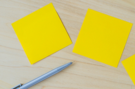 Yellow paper notes with pen on the wood table photo