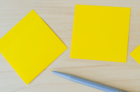 Yellow paper note with pen on the wood table photo